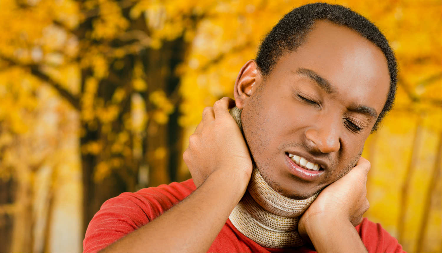 man with a neck brace holding his neck